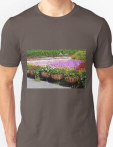 Many flowers in the park. Beautiful flower pots along the alley. T-Shirt