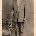 Man standing with chair. by Vintaged