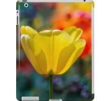 A yellow tulip flower set against a colourful background iPad Case/Skin