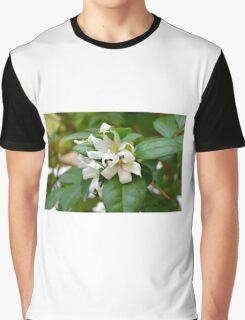 Macro on small beautiful white flowers on green leaves. Graphic T-Shirt