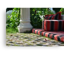 Mattress in the park and white classical column next to green leaves. Canvas Print