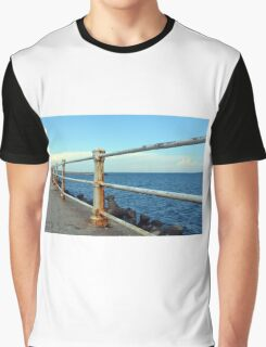 The sea and promenade with rusty white handrail. Graphic T-Shirt