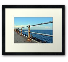 The sea and promenade with rusty white handrail. Framed Print