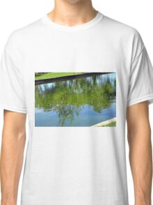 Trees reflected in the water in the park. Classic T-Shirt