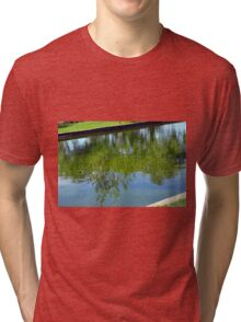 Trees reflected in the water in the park. Tri-blend T-Shirt