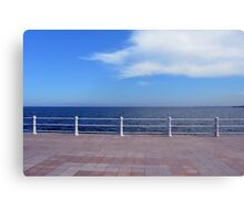 Promenade by the sea with cloudy sky and white handrail. Canvas Print