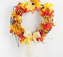Autumn wreath hanging on a bright door by 3523studio