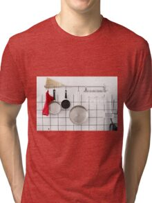 Frying pans hang on a wall of a domestic kitchen  Tri-blend T-Shirt