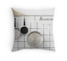 Frying pans hang on a wall of a domestic kitchen  Throw Pillow