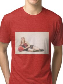 arrogant model in red corset reclining on a black leather couch  Tri-blend T-Shirt