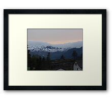 Sunset behind the clouds over the snow covered mountains Framed Print
