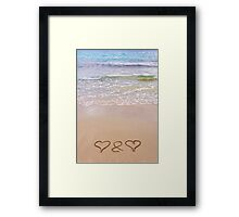 Two hearts drawn in the sand on a beautiful beach Framed Print