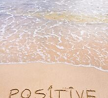 Positive Thinking message written on sand, with waves in background by Stanciuc