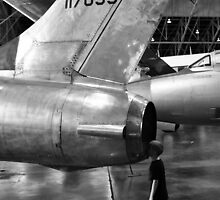 Boy looking into jet airplane thruster black and white by Jason Franklin