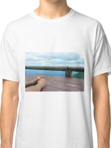 Man hands on a wooden table outside, with cloudy sky. Classic T-Shirt