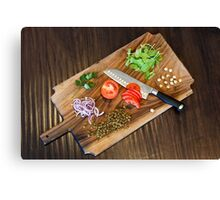 Freshly cut vegetables on a cutting board with a chef's knife  Canvas Print