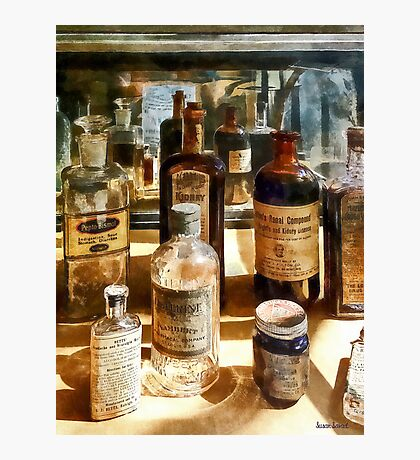 Medicine Bottles in Glass Case Photographic Print