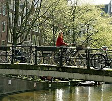 Girl Riding a bicycle over a Canal in Amsterdam by Rosebuds