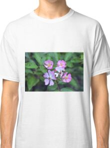 Small purple flowers on green leaves background. Classic T-Shirt