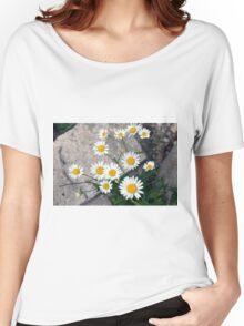 Beautiful small white flowers on the pavement. Women's Relaxed Fit T-Shirt