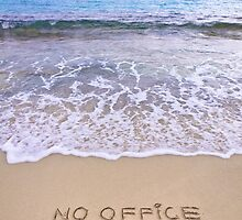 No office required written on sand, blue ocean water in background by Stanciuc