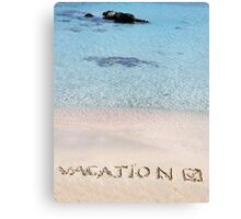 Vacation and checked mark written on sand on a beautiful beach, blue waves in background Canvas Print