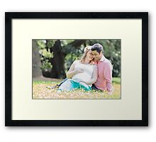 Pregnant woman with her husband in the garden Framed Print
