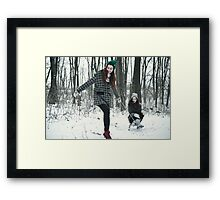 Two women are playing in the snow Framed Print