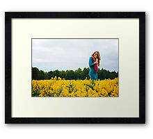 Blonde woman in a yellow flowers field Framed Print