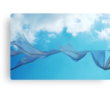Cloth in the wind against the blue cloudy sky. Canvas Print