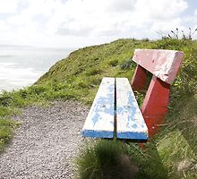 view of beach and sea in Ballybunion with bench by morrbyte