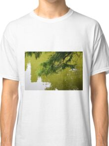 Tree branch leaning over a green lake. Classic T-Shirt