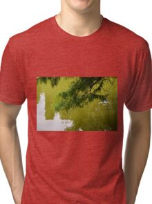 Tree branch leaning over a green lake. Tri-blend T-Shirt