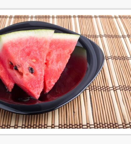 Slices of red watermelon on a black plate on a bamboo mat Sticker