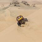 Dune buggy with passengers speeding across the side of a large dune by Ben Ryan
