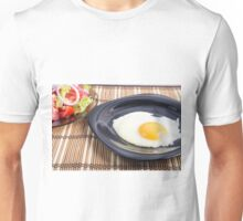 Closeup view on fried eggs with yolk on a black plate Unisex T-Shirt