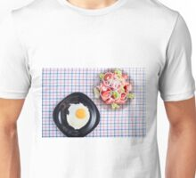 Top view on a black plate with a fried egg and a small portion of tomato salad Unisex T-Shirt