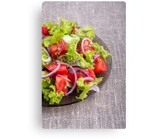 Fragment of a transparent plate with a fresh salad of raw vegetables Canvas Print