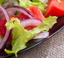 Side view on a diagonal on a plate with fresh salad of raw vegetables closeup Sticker