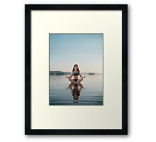 Woman practicing meditation sitting on platform in the water art photo print Framed Print