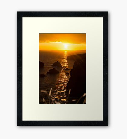 sunset over the coastal rocks with wild highl Framed Print