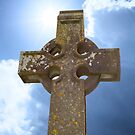 sunshine over celtic cross at ancient graveyard by morrbyte