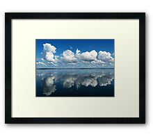 Brilliant white clouds in a rich azure-blue sky reflected in smooth sea. Framed Print