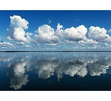Brilliant white clouds in a rich azure-blue sky reflected in smooth sea. Photographic Print