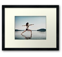 Woman practicing yoga on the water doing Warrior pose over blue sky art photo print Framed Print