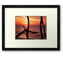 Colorful red sunset behind driftwood sculpture art photo print Framed Print
