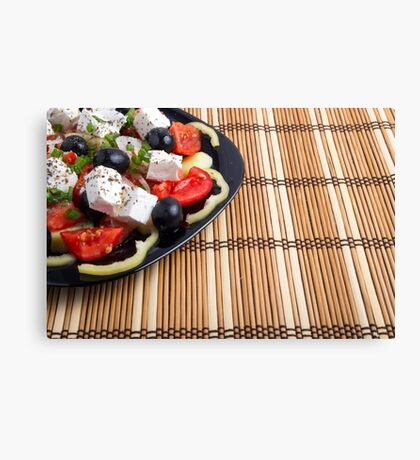 Side view of the Greek vegetarian salad of tomatoes, cucumbers, onions, olives, peppers and feta cheese Canvas Print