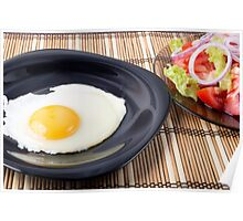 Fried eggs with yolk on a black plate and a salad Poster