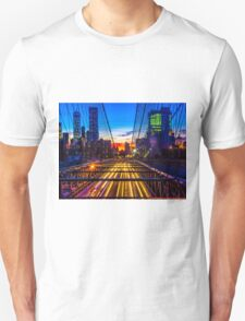 Sunset over the Brooklyn Bridge facing manhattan with lights of passing by cars underneath  Unisex T-Shirt