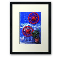 Geranium and red wheels on the blue wall Framed Print